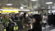 Commuters waiting to pass the ticket gate at the JR Shinjuku Station