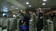 Commuters walking through ticket barriers in London Underground Tube Station