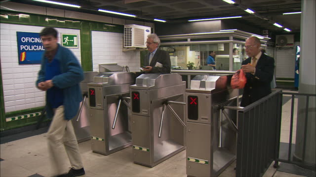 WS Commuters walking through turnstiles in subway station, Madrid, Spain