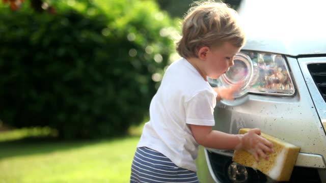 Comp of cute toddler boy washing a car