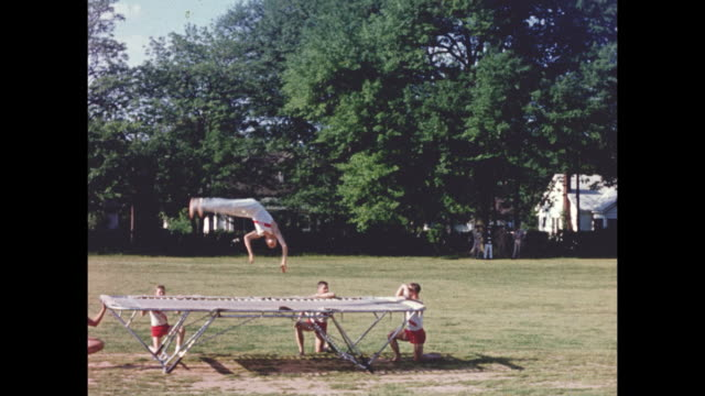 A competative student trampoline team jumping on a trampoline outdoors on a sunny day.