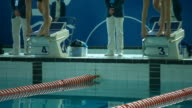 MS SLO MO Competitive swimmer diving into pool off of his starting podium in high speed / United Kingdom