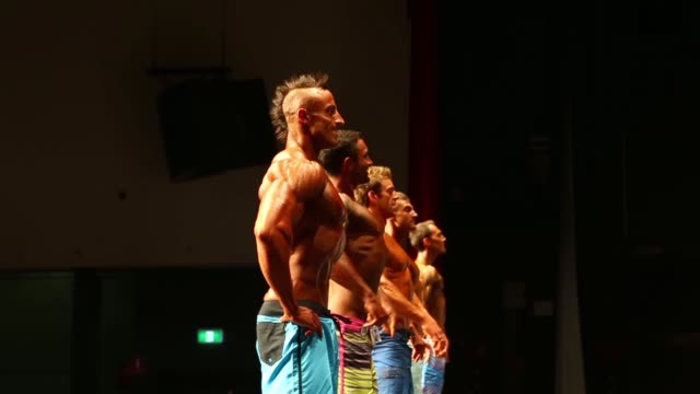 Competitors in the Men's Physique division pose on stage during the 2014 IFBB Victorian Bodybuilding Championship on October 05 2014 in Melbourne...