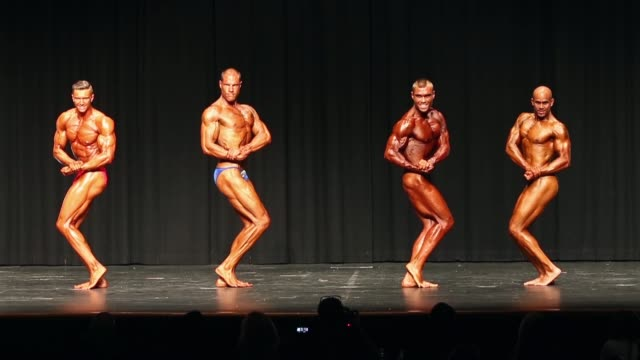 Competitors pose on stage during the 2014 IFBB Victorian Bodybuilding Championship on October 05 2014 in Melbourne Australia