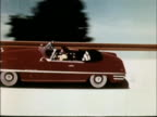 / Compilation of various passenger cars on banked or curved tracks / Sequence of 1949 Chevrolet approaching and driving on banked track / Twoshot...