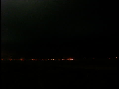 Compilation Oil fires burning under pitch black sky / Oil fires burning in the distance under grey skies /360 degree pan of oil fires burning moving...