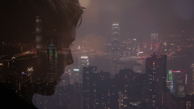 Compisite image of man looking out over city at night
