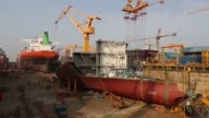 Components of a ship sit under construction in a dry dock at the Daewoo Shipbuilding Marine Engineering Co DSME shipyard in Geoje A worker welds the...