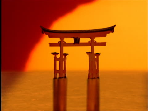 Composite wide shot zoom in time lapse sun setting behind Miyajima Itsukushima torii on water / Japan
