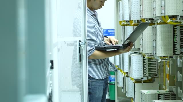 Computer technician inspects fiber patch cord
