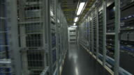 Computers fill rows of racks in a large server room.