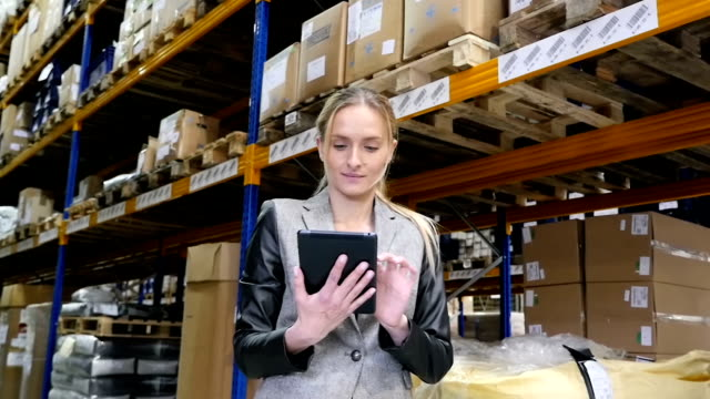 Concentrated woman working with the tablet in warehouse