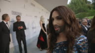 INTERVIEW Conchita Wurst on being at AmfAR at AmfAR Red Carpet at Hotel du CapEdenRoc on May 22 2014 in Cap d'Antibes France