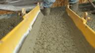 Beton fließt von Mischpult Trog die Arbeiter mit Schaufel
