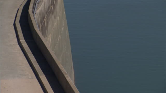 A concrete retainer wall lines a road at the top of a concrete flood control dam.