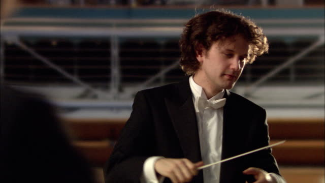MS Conductor holding baton leading orchestra, smiling / London, United Kingdom