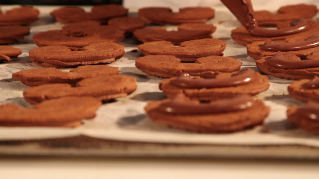 Confectioner positioning chocolate cookies on baking tray