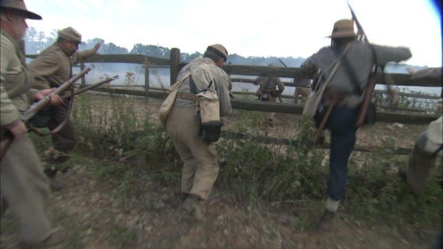 Confederate soldiers climb split-rail fences in a Civil War reenactment.