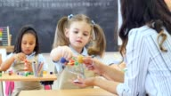 Confident Caucasian female kindergarten student learns about the solar system