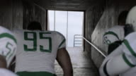 MS SLO MO. Confident football players run through stadium tunnel entrance at start of professional football game.