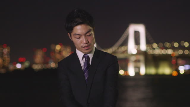 MS Confident Japanese businessman adjusts tie and looks at camera / Tokyo, Japan