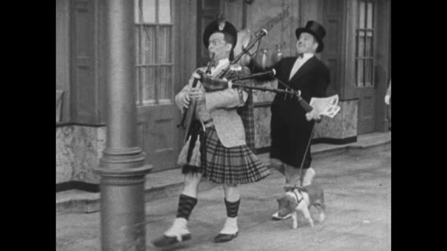 Confident Bobby Clark, dressed in kilt, plays bagpipes on street as Paul McCullough hands out fliers