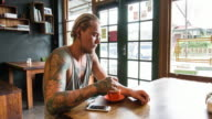 Confident man with tattoos drinking coffee