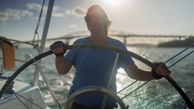 Confident mature female in control of the helm wheel of luxury sailing yacht