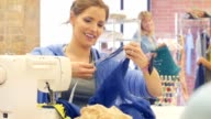 Confident mid adult Caucasian female fashion designer uses a sewing machine in her workshop