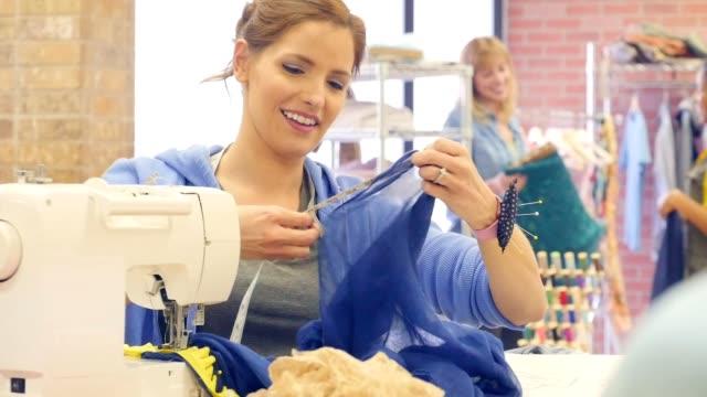 Zuversichtlich Mitte Erwachsenen kaukasischen weibliche Mode-Designer verwendet eine Nähmaschine in ihrem Atelier