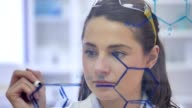 Confident scientist concentrates while drawing molecular structure on transparent board