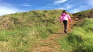 Confident young girl climbing on a steep hill