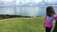 Confident young girl looks at a view from a high hill