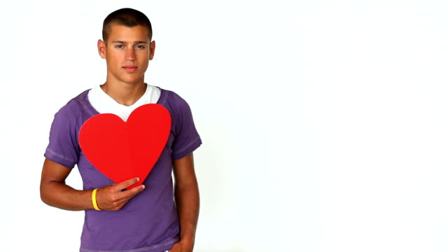 Confident young man holding heart shape