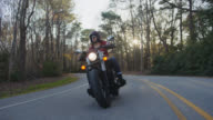 SLO MO. Confident young woman drives motorcycle down empty forest road as setting sun peaks through trees.