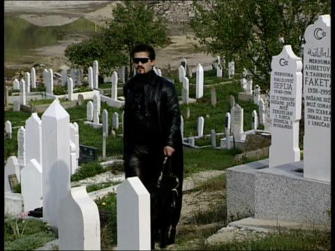 Conflict Blinded man returns BONGS Sead Bekric along thru cemetery ITN BOSNIAHERZEGOVINA Srebrenica LMS Sead Bekric blinded by Serbian shell during...