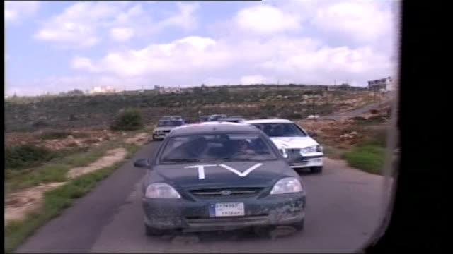Day 17 shelling of Southern Lebanon continues LEBANON Tyre to Rmaish road SHOTs from moving car showing convoy of voluntary workers' and television...