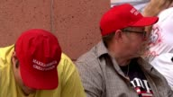 Donald Trump commits more troops to Afghan war Arizona Phoenix EXT Two men wearing red 'Make America Great Again' baseball caps Man along selling...