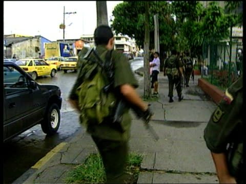 Effects of Civil War on Population ITN COLOMBIA Cali Traffic slong street CBV Soldier standing guard on street as traffic past Soldiers on street PAN...