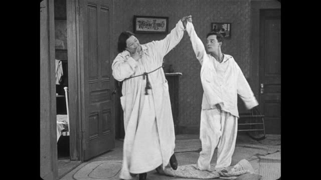 Confused Buster Keaton is awakened by amorous woman, who happily skips him from the room in his pajamas
