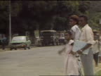 1989 VS Congo woman walking smiling w/ huge bowl of food man woman child hailing car for a ride pan from Caucasian hair products on display to...