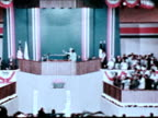 Congresswoman Barbara Jordan standing on stage waving to crowd HOUSE JUDICIARY COMMITTEE Barbara behind microphone speaking