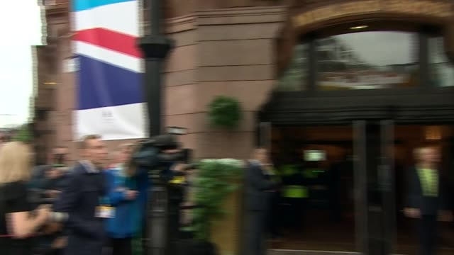 Theresa May arrival ENGLAND Manchester EXT Steam rising from basement / press waiting / car pulls up / Theresa May MP and Philip May from car along...
