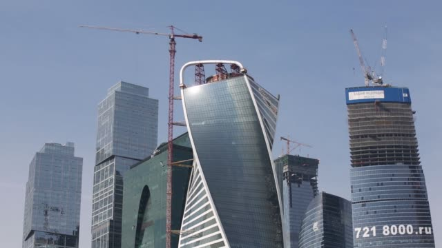 A construction crane stands next to the Evolution Tower and other skyscrapers in the Moscow International Business Center also known as Moscow City...