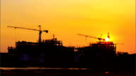 Construction cranes and building with sunset,Time lapse