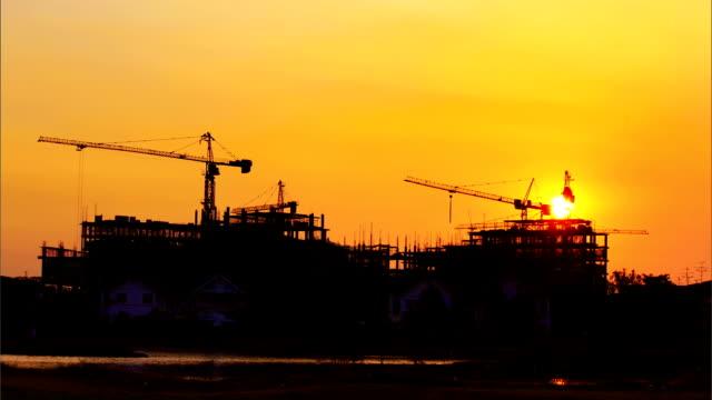 Konstruktion cranes und Gebäude bei Sonnenuntergang, Zeitraffer