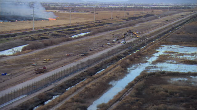 LOW AERIAL Construction crew at work, building section of new 'border wall' along US-Mexican border at El Paso, Texas, USA