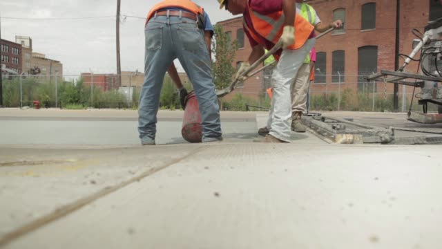 Construction crew workers shovel extra asphalt into bucket on Chicago's south side