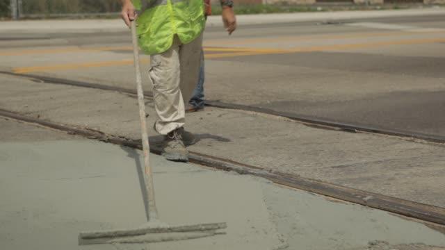 Construction crews apply and level asphalt