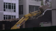 Construction excavator pulls out large chucks of brick wall in Brooklyn, New York City.